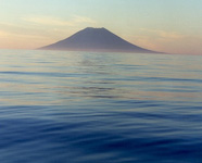 Photograph of a volcanic island arising from a calm sea